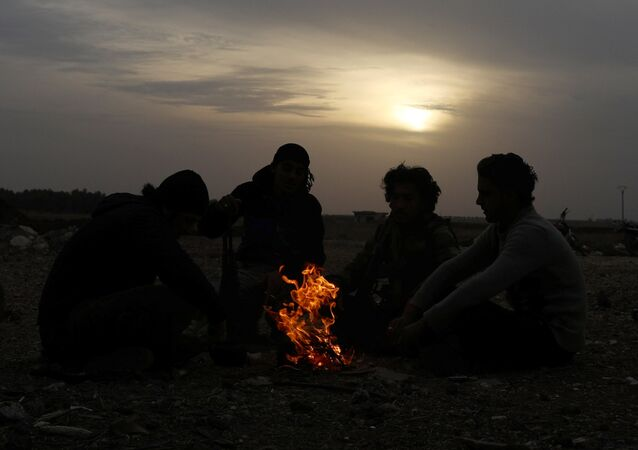 Free Syrian Army fighters sit together around a bonfire in the rebel-held town of Dael, Syria December 22, 2017