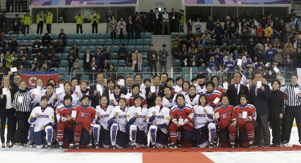 FILE - In this April 6, 2017, file photo, women's ice hockey players of South Korea, in white, and North Korea, in red, pose for a photo with International Ice Hockey Federation officials after their Ice Hockey Women's World Championship Division II Group A game in Gangneung, South Korea. North and South Korea agreed on Monday, Jan. 15, 2018, in principle to field a joint women's ice hockey team during next month's Olympics in South Korea, and relayed their position to the International Olympic Committee