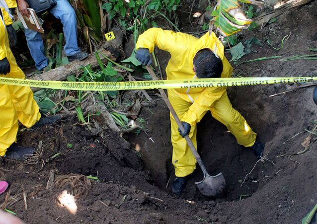 In this Jan. 15, 2018 photo, released by the General Prosecutor of Nayarit, a man digs up a clandestine grave in Xalisco, Nayarit state, Mexico