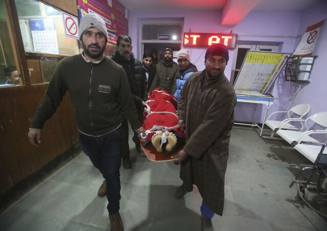 Kashmiri villagers and policemen carry the body of a Swedish skier who has been identified as 25-year-old Daniel Akesson inside a hospital in Tangmarg, near the tourist town of Gulmarg, Jammu and Kashmir, India, Thursday, Jan. 18, 2018