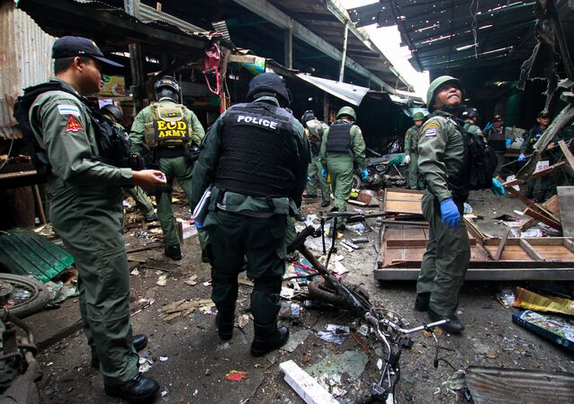 Military personnel and police officers inspect the site of a bomb attack at a market in the southern province of Yala, Thailand, January 22, 2018