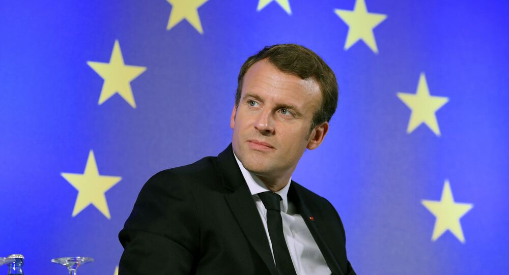French President Emmanuel Macron looks on as he sits in front of a flag of the European Union during an open debate on Europe on October 10, 2017 at the Goethe University in Frankfurt am Main, western Germany
