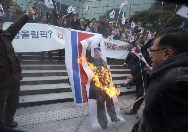 South Korean protesters burn a portrait of North Korean leader Kim Jong Un during a rally against a visit of North Korean Hyon Song Wol, head of a North Korean art troupe, in front of Seoul Railway Station in Seoul, South Korea, Monday, Jan. 22, 2018