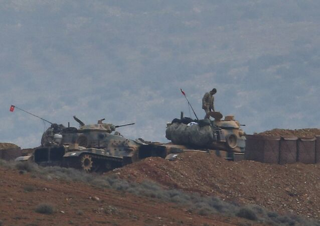 Soldiers man a Turkish Army artillery position, as seen from the outskirts of the village of Sugedigi, Turkey, near the border with Syria, background