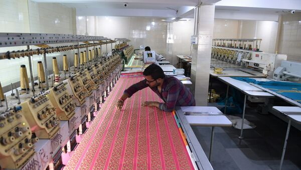 An Indian textile maker works on an embroidery machine at a workshop in Ahmedabad. (File) - Sputnik International