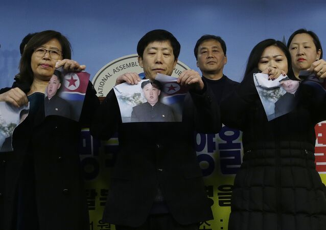 North Korean defectors tear portraits of North Korean leader Kim Jong Un during a press conference against the North Korea's participation in the 2018 Pyeongchang Winter Olympics at the National Assembly in Seoul, South Korea, Wednesday, Jan. 24, 2018