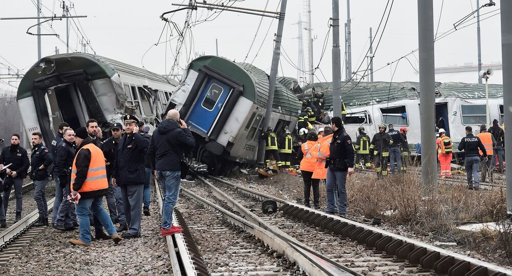 Rescue workers and police officers stand near derailed trains in Pioltello, on the outskirts of Milan, Italy, January 25, 2018
