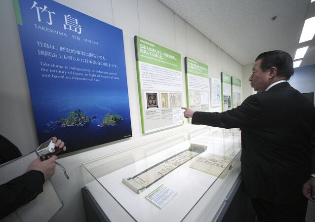 Tetsuma Esaki, minister in Charge of Territorial Issues, watches a photo of the island known as Takeshima in Japanese and as Dokdo in Korean, claimed by both Japan and South Korea, at the National Museum of Territory and Sovereignty in Tokyo Thursday, Jan. 25, 2018