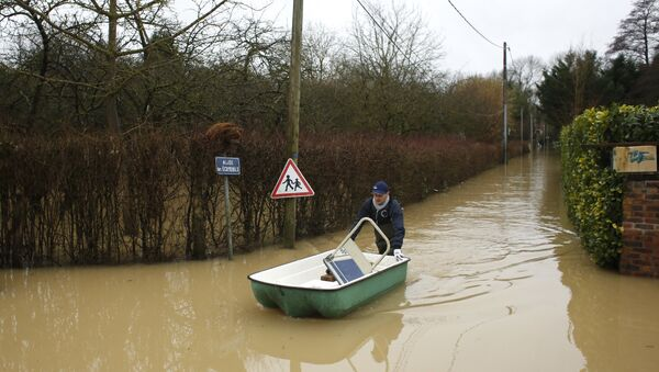 A resident pushes a dinghy boat in a flooded street of Esbly, east of Paris, where the Grand Morin river floods - Sputnik International