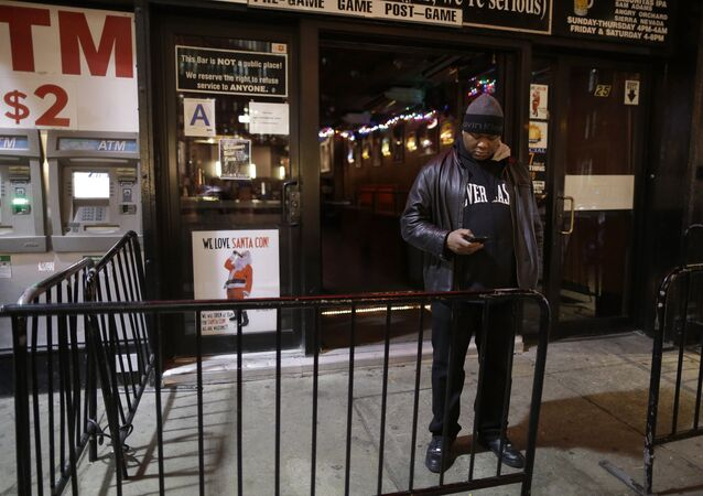 In this Wednesday, Dec. 9, 2015, photo a bouncer stands next to a sign professing love for Santacon hanging in the window of the Continental bar in New York