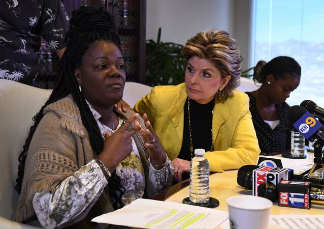 Essie Grundy (L) sits beside attorney Gloria Allred as they announce their race discrimination lawsuit against retail giant Walmart in Los Angeles, California on January 26, 2018