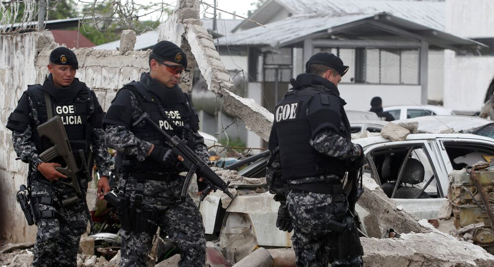 Police officers walk past damaged vehicles at the scene of a bomb explosion at a police station in San Lorenzo