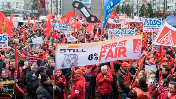 German metalworkers hold banners and flags during a demonstration for higher pay on January 24, 2018 in Hamburg, northern Germany - Sputnik International