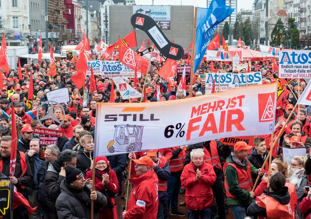 German metalworkers hold banners and flags during a demonstration for higher pay on January 24, 2018 in Hamburg, northern Germany