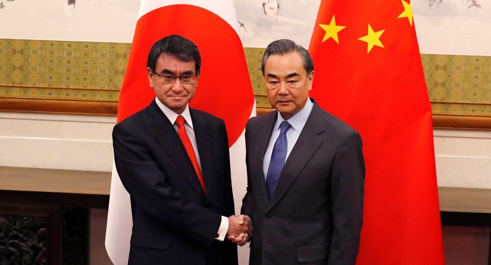 Japanese Foreign Minister Taro Kono, left, and Chinese counterpart Wang Yi pose for photograph before their meeting at the Diaoyutai State Guesthouse in Beijing, China Jan. 28, 2018