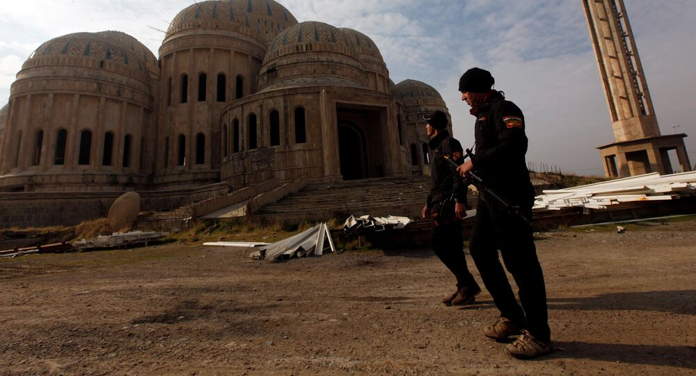 Iraqi Counter-Terrorism Service (CTS) members walk past a mosque during a battle with Daesh militants in east of Mosul, Iraq