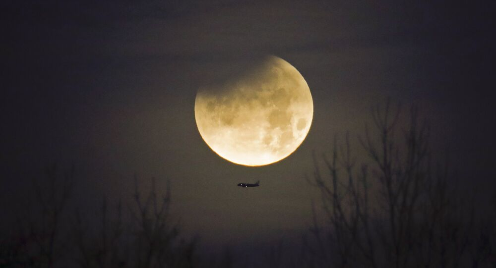 A plane passes by as the moon sets over trees during a phenomena that combined a supermoon, a blue moon and a lunar eclipse in Charlotte, N.C., Wednesday, Jan. 31, 2018