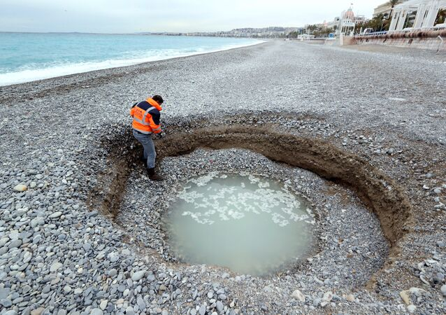People looks at a two-metre deep and five-meter wide crater, filled with brackish water, which has formed on the beach of Lido on the French riviera city of Nice on February 1, 2018
