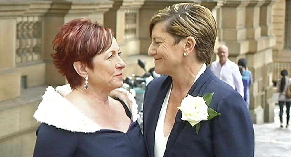 In this image made from Australia Broadcasting Corporation video, Christine Forster looks at her partner Virginia Edwards, Feb. 2, 2018, in Sydney, Australia