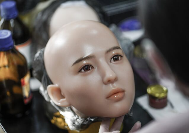 This photo taken on February 1, 2018 shows a worker painting the face of a silicone doll at a factory of EXDOLL, a firm based in the northeastern Chinese port city of Dalian
