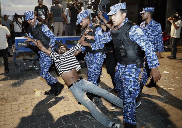 Maldivian police officers detain an opposition protestor demanding the release of political prisoners during a protest in Male, Maldives, Friday, Feb. 2, 2018