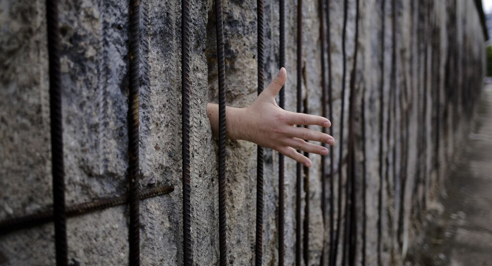 A tourist from the Netherlands puts his hand through a hole of the remains of the Berlin Wall to over a hand shake, at the Berlin Wall memorial at Bernauer Strasse in Berlin, Sunday, Aug. 13, 2017