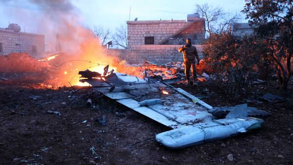 A picture taken on February 3, 2018, shows a Rebel fighter taking a picture of a downed Sukhoi-25 fighter jet in Syria's northwest province of Idlib - Sputnik International