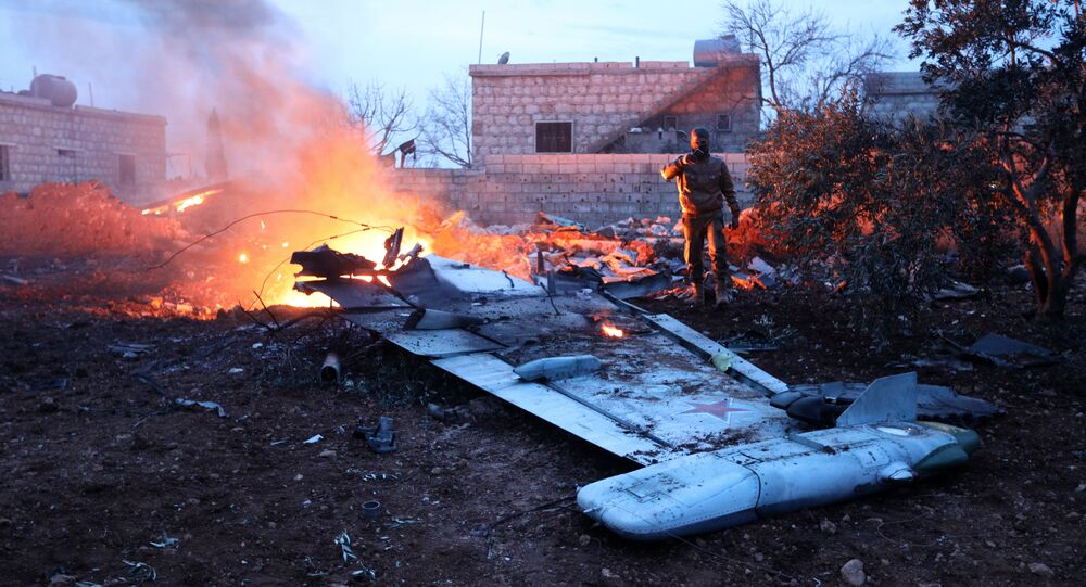 A picture taken on February 3, 2018, shows a Rebel fighter taking a picture of a downed Sukhoi-25 fighter jet in Syria's northwest province of Idlib