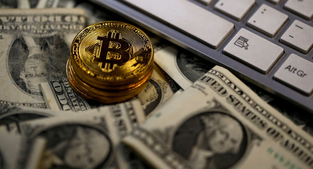 Bitcoin (virtual currency) coins placed on Dollar banknotes, next to computer keyboard, are seen in this illustration picture, November 6, 2017