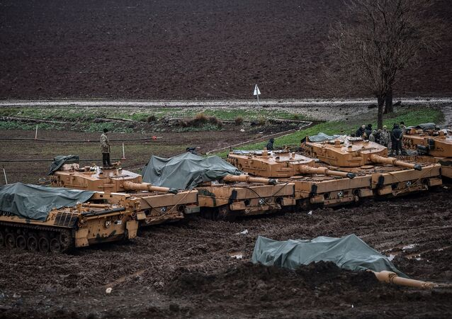 Turkish soldiers stand on their German-made Leopard 2A4 battle tanks stationed in a field near the Syrian border at Hassa, in Hatay province