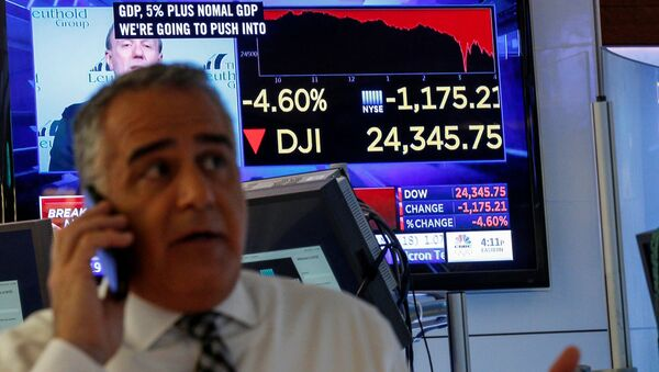 A trader works on the floor following the closing bell as a screen shows the Dow Jones Industrial Average on the New York Stock Exchange, (NYSE) in New York, U.S., February 5, 2018 - Sputnik International