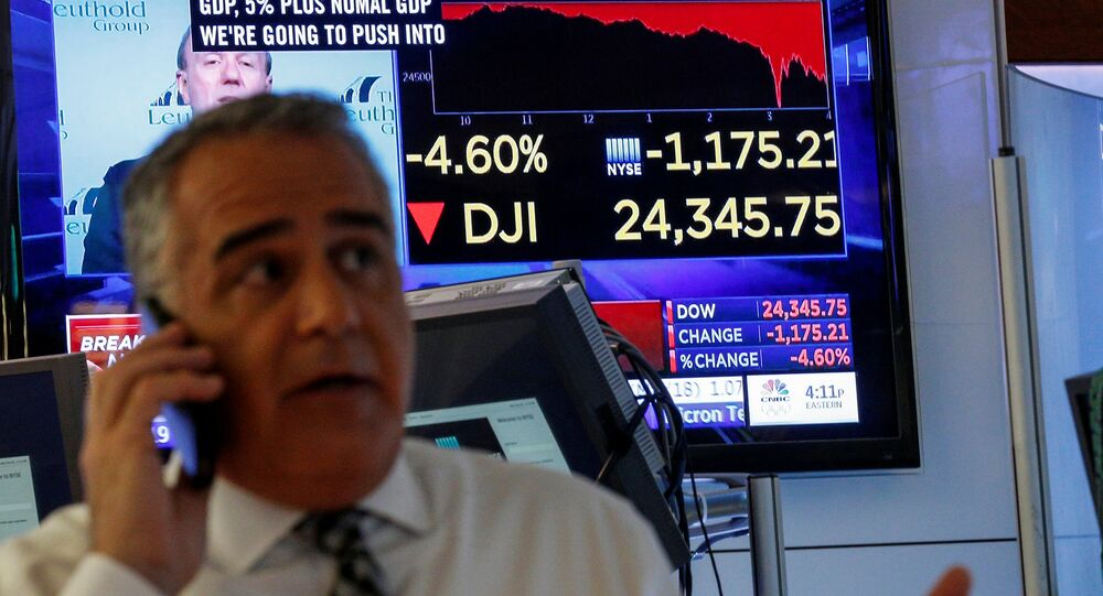 A trader works on the floor following the closing bell as a screen shows the Dow Jones Industrial Average on the New York Stock Exchange, (NYSE) in New York, U.S., February 5, 2018