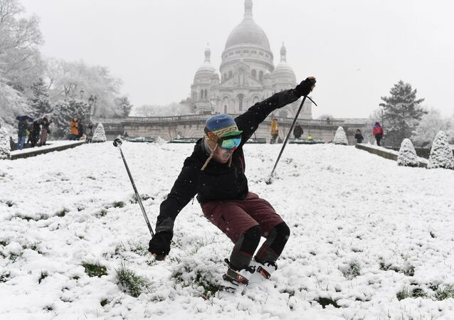 A man is skiing on the snow-covered Montmartre hill in front of the Basilica of the Sacred Heart (Basilique du Sacre-Cœur) on February 6, 2018 in Paris