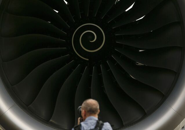 A visitor takes a photo of the Rolls-Royce jet engine of the Airbus A350-1000 parked at the static display area during the Singapore Airshow on Wednesday, Feb. 7, 2018, in Singapore.
