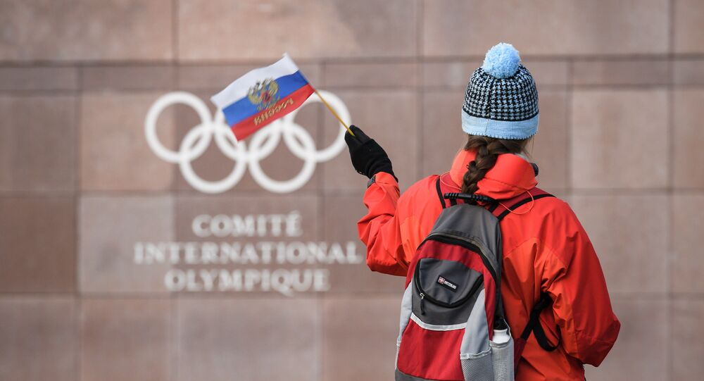 A supporter waves a Russian flag in front of the logo of the International Olympic Committee (IOC) at their headquarters on December 5, 2017 in Pully near Lausanne