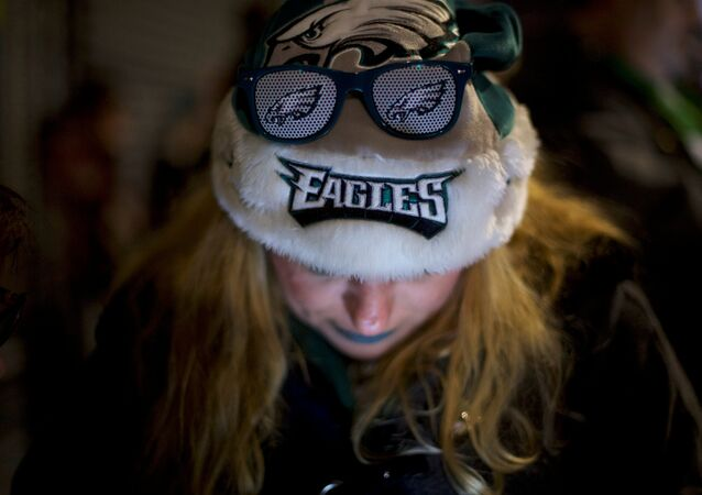 A smartphone illuminates a fan's face after the Philadelphia Eagles'  Super Bowl victory over the New England Patriots on February 4, 2018