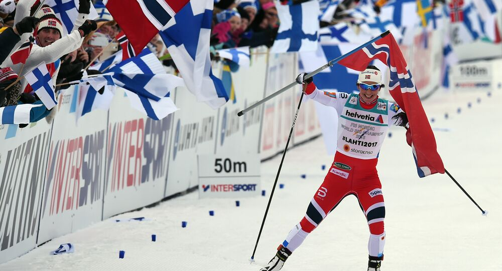 Norwegian Marit Bjoergen takes the Norwegian flag as she arrives in the finish are aof the cross country ladies 4 x 5 km relay classic and free style competition of the 2017 FIS Nordic World Ski Championships in Lahti, Finland, on March 2, 2017