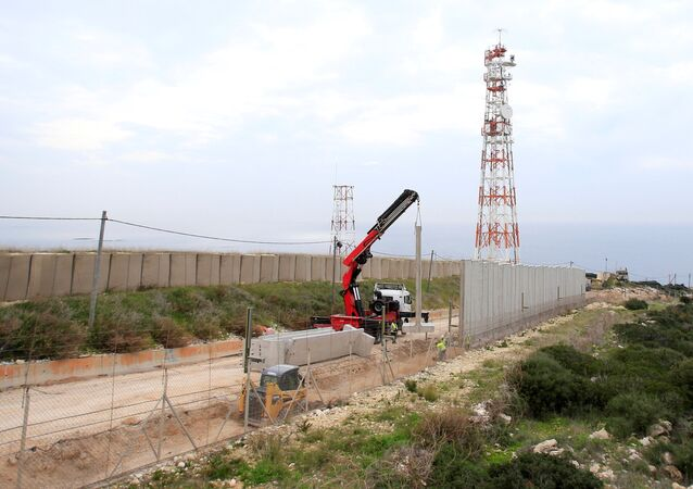 Israeli workers are seen building a wall near the border with Israel near the village of Naqoura, Lebanon February 8, 2018