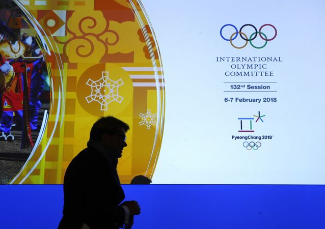 A member of the International Olympic Committee walks past a display during the 132nd IOC Session prior to the 2018 Winter Olympics in Pyeongchang, South Korea, Wednesday, Feb. 7, 2018
