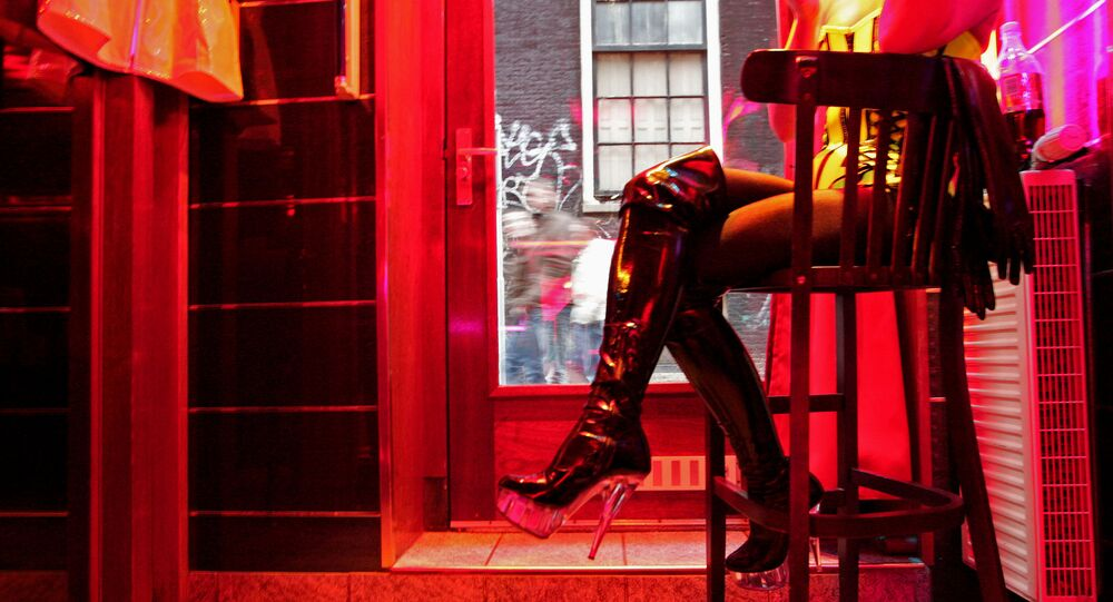 Prostitute waiting for clients behind her window in Amsterdam's red-light distric (File)