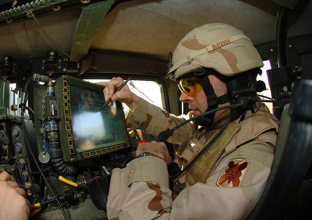 A U.S. soldier preparing his Blue Force Tracker before departing Camp Victory, Iraq in 2005
