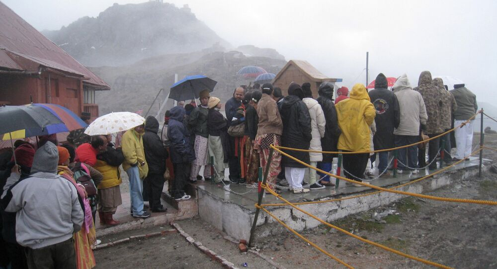 Indian tourists stand in queue in rain to visit the India-China border at Nathu-La, a 14,200 feet high pass, about 51 kilometers(38.69 miles) east of Gangtok, India, Thursday, June 5, 2008