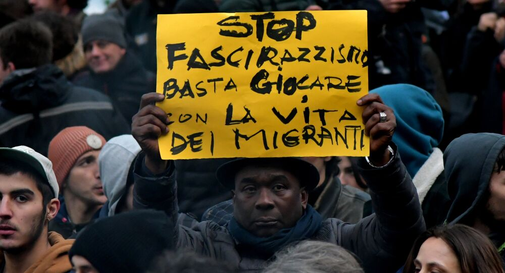A protester holds a placard reading stop to the fascism and racism, stop playing with the migrants' life during an anti-racism demonstration one week after an attack that injured at least six migrants, on February 10, 2018 in Macerata