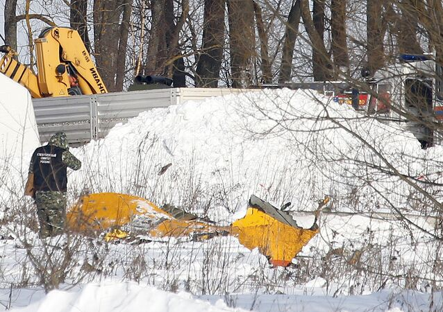 A man looks at wreckage near the scene of a AN-148 plane crash in Stepanovskoye village, about 40 kilometers (25 miles) from the Domodedovo airport, Russia