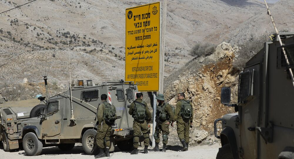 Israeli soldiers stand guard near the Israeli Syrian border next to the town of Majdal Shams in the Israeli-occupied sector of the Golan Heights