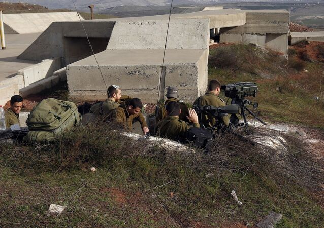 A picture taken on February 10, 2018 show Israeli solders taking positions in the Israeli-occupied Golan Heights near the border with Syria