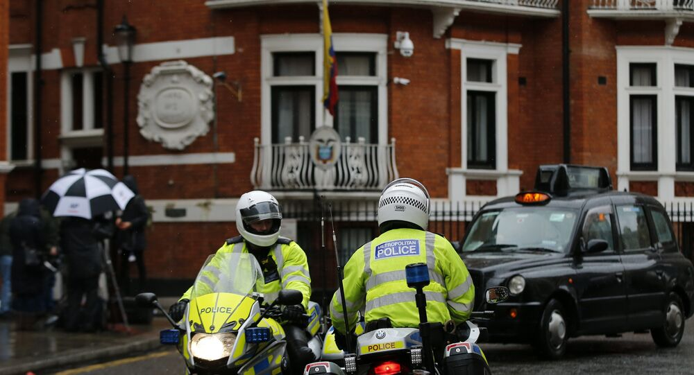 Police motorcyclists briefly stop outside the Ecuadorian embassy in London