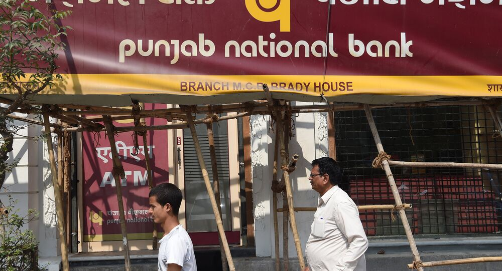 Indian men walk past signage for the state-owned Punjab National Bank (PNB) in Mumbai on February 14, 2018