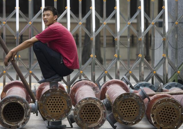 A Chinese man pause as he waits for steel pipes to be loaded onto a truck in Beijing, China. (File)