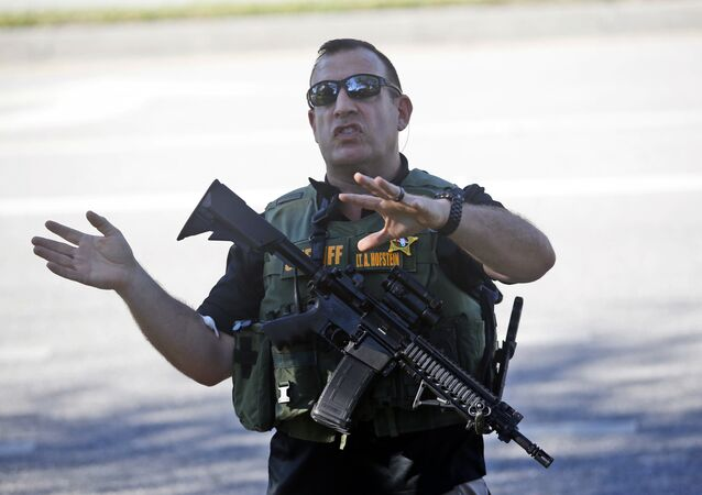 A law enforcement officer tells anxious family members to move back, Wednesday, Feb. 14, 2018, in Parkland, Fla.